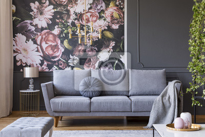 Poster Blanket on grey couch in living room interior with flowers wallpaper and lamp on table. Real photo