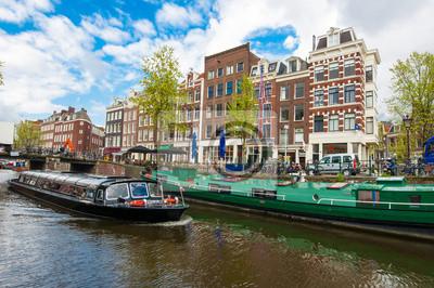 Bootsfahrt durch Amsterdam-Kanäle mit Hausbooten entlang des Kanals, Niederlande.
