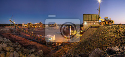 Poster Bulldozer loading rocks into the crusher within the copper mine head at dusk in NSW Australia
