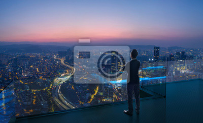 Poster Businessman standing on open roof top balcony watching city night view . Business ambition and vision concept .