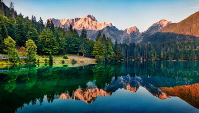 Poster Calm morning view of Fusine lake. Colorful summer sunrise in Julian Alps with Mangart peak on background, Province of Udine, Italy, Europe. Beauty of nature concept background.