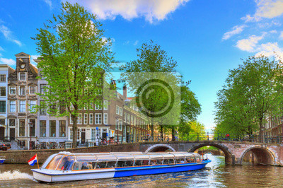 Canal Cruise Boot geht unter der Brücke über den Leidse-Kanal am Patrizier- oder Lords-Kanal (Herengracht) in Amsterdam im Frühjahr