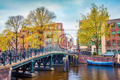 Captivating autumn scene of Amsterdam city. Famous Dutch channels and great cityscape. Gloomy morning landscape in Netherlands, Europe. Traveling concept background.