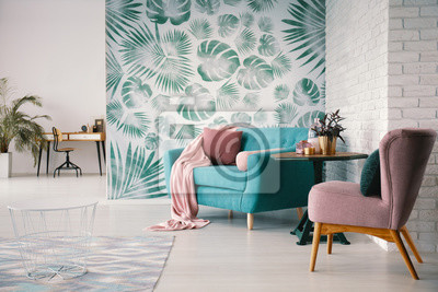 Poster Chair and turquoise sofa in green living room interior with leaves wallpaper and table. Real photo