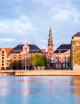 Charming view of the houses and spire of Our Savior Church on the waterfront of Copenhagen, Denmark. Exotic amazing places. Popular tourist atraction.