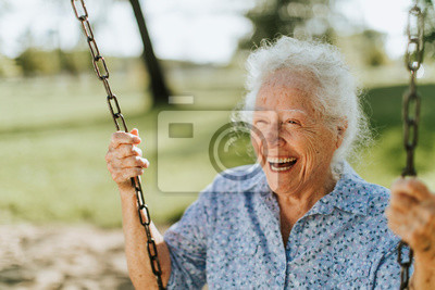 Poster Cheerful senior woman on a swing at a playground