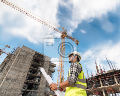 Poster Civil engineer checking work with  construction drawing at building site of highrise building