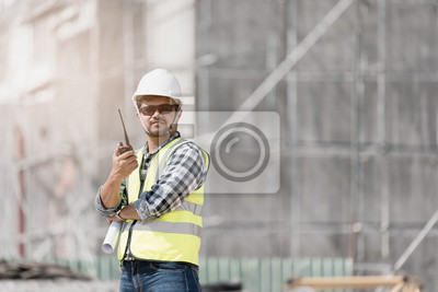Poster Civil engineer checking work with walkie-talkie for communication to management team in the construction site