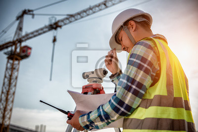 Poster Civil Engineering, Surveyor people making on construction site and holding blueprint in his hand for checking with surveying telescope instrument