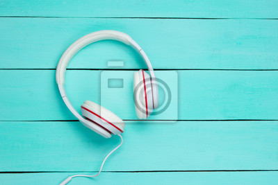 Poster Classic white wired headphones on blue wooden background. Retro style. 80s. Pop culture. Top view. Minimal Music Concept