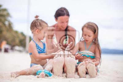 Close-up der Füße der Mutter und zwei Töchter auf dem weißen