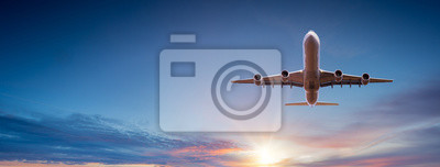 Poster Commercial airplane flying above dramatic clouds during sunset.