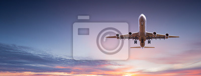 Poster Commercial airplane jetliner flying above dramatic clouds.