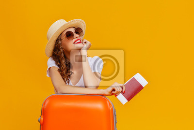 Poster concept of travel. happy woman girl with suitcase and  passport on  yellow background.