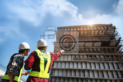 Poster Construction engineers discussion with consultant at construction site or building site of highrise building with blueprints.