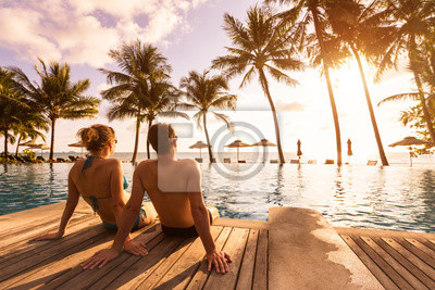 Poster Couple enjoying beach vacation holidays at tropical resort with swimming pool and coconut palm trees near the coast with beautiful landscape at sunset, honeymoon destination