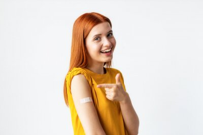 Poster Covid-19 vaccinated caucasian happy smiling young woman showing arm with plaster, gray background