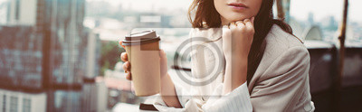Poster cropped view of thoughtful fashionable girl in beige suit posing on roof with coffee to go