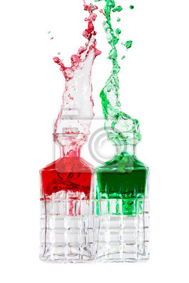Crystal bottles splashing red and green liquid against a white background