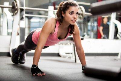 Poster Cute Brunette arbeitet in einem Fitnessstudio