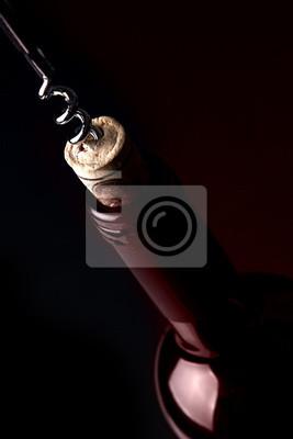 Das Öffnen einer Flasche Wein, auf dunklem Hintergrund. Red Reflexion.