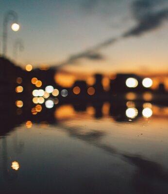 Poster Defocused Image Of Illuminated Lights On Wet Street At Night
