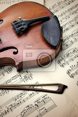 Detail of old scratched violin on music sheet. Vintage style.