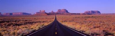 Poster Dies ist Straße 163, die durch die Navajo Indian Reservation läuft. Die Straße verläuft die Mitte und wird kleiner in die Unendlichkeit. Die roten Felsen der Monument Valley sind im Hintergrund. Die P