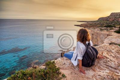 Poster Ein stilvoller Reisender der jungen Frau passt einen schönen Sonnenuntergang auf den Felsen auf dem Strand, Zypern, Kap Greco, ein populärer Bestimmungsort für Sommerreise in Europa auf