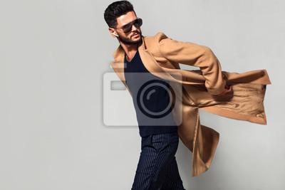 Poster Elegant young handsome main coat wearing glasses. Studio fashion portrait.