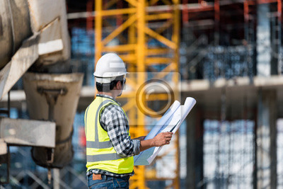 Poster Engineering Consulting people on construction site holding blueprint in his hand. Building  inspector. Construction site check drawing and business workflow of new building
