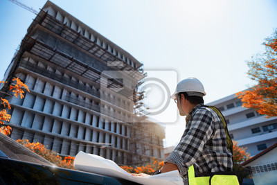 Poster Engineering Consulting People on construction site holding blueprint in his hand. Building inspector. Construction site check drawing and business workflow of new highrise building.