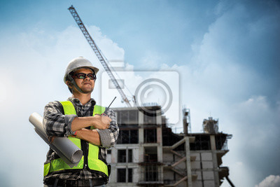 Poster Engineers People holding blueprint in his hand at construction site or building site of highrise building