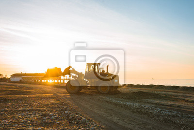 Poster Excavator loads the excavation onto a truck (hydraulic)are heavy construction equipment consisting of an arrow,a bucket and a cabin on a rotating platform.On the beach with the sea and the setting sun