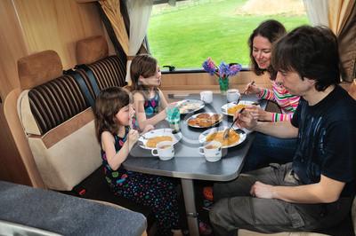 Familie beim Essen in RV innen, Reise in Wohnmobil in den Urlaub