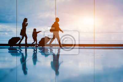 Poster Family at airport travelling with young child and luggage walking to departure gate, girl pointing at airplanes through window, silhouette of people, abstract international air travel concept