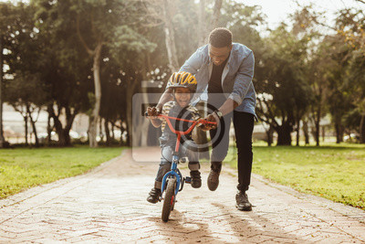 Poster Father teaching his son cycling at park