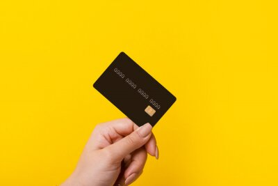 Poster Female hand holding credit card on yellow background