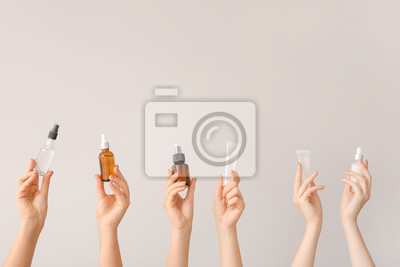 Poster Female hands with different cosmetic products in bottles on grey background