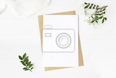 Poster Feminines Hochzeitsbriefpapier, Desktop-Mock-up-Szene.  Leere Grußkarte, Bastelumschlag, Atemblumen des Babys, Seidenband und Linsenzweige.  Alter weißer hölzerner Tischhintergrund.  Flache Lage, Drau