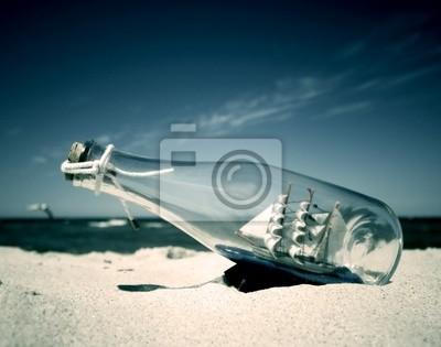 Flasche mit Schiff im Inneren am Strand liegen. Konzeptionelle Bild