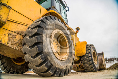 Poster Focus on the black rubber wheels of a yellow bulldozer at a construction site