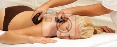 Frau bekommen Massage mit heißen Steinen