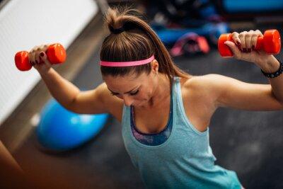 Poster Frau hebt Gewichte und arbeitet an ihren Schultern in der Turnhalle