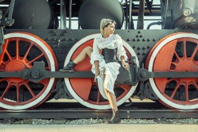 Poster Frau im Vintage-Kleid sitzt auf der Lokomotive das Rad.