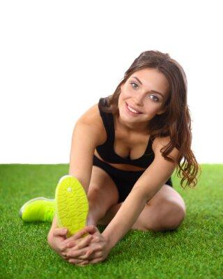 Poster Frau macht Dehnübungen auf dem grünen Rasen