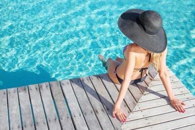 Poster Frau sitzt auf dem Deck am Pool