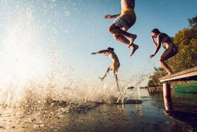 Poster Friends having fun enjoying a summer day swimming and jumping at the lake.
