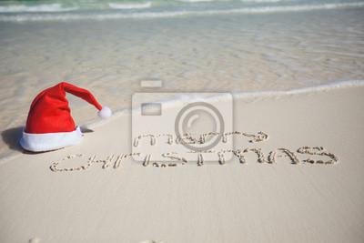 Frohe Weihnachten am tropischen Strand mit weißem Sand weihnachten geschrieben
