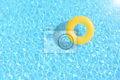 Poster Gelber Schwimmbeckenring im blauen Wasser. Konzept Farbe Sommer.